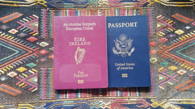 An Irish and United States passport sitting on top of a geometric Navajo weaving.