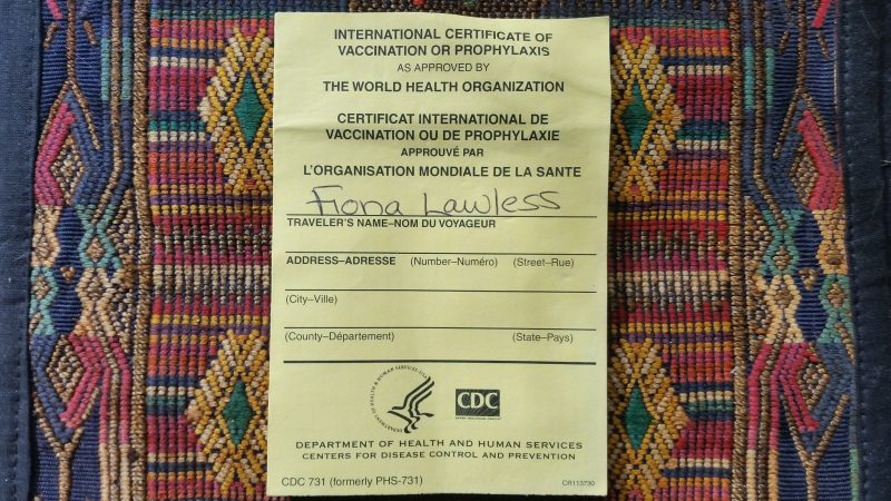 An official yellow International Certificate of Vaccination issued from the CDC on top of a Navajo weaving.