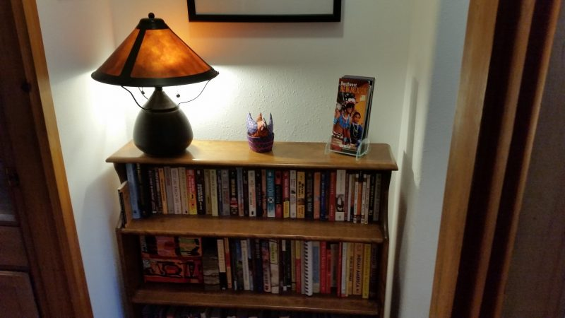 A fully-stocked book shelf with a lamp on top of it.