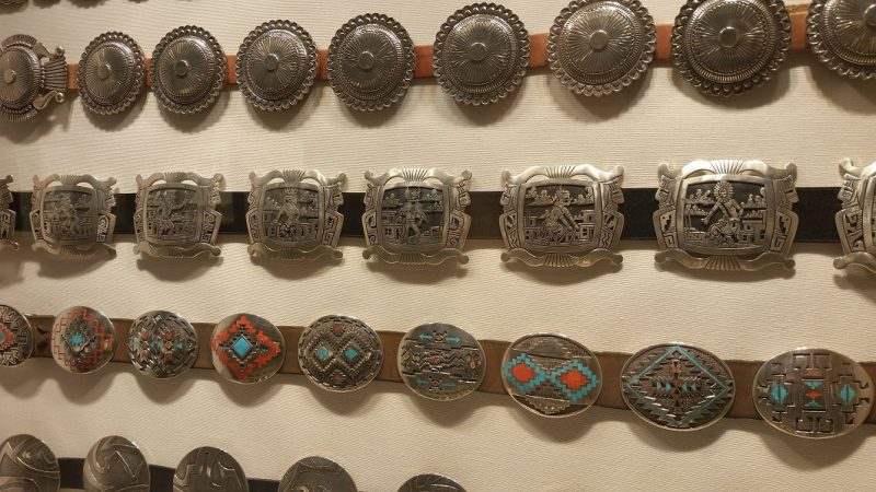 A display of many intricate silver belt buckles from Museum Hill in Santa Fe.