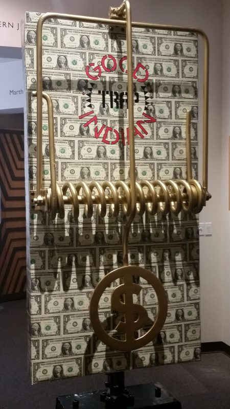 An art installation from Bob Haozous of a large mousetrap lined with US $1 bills.