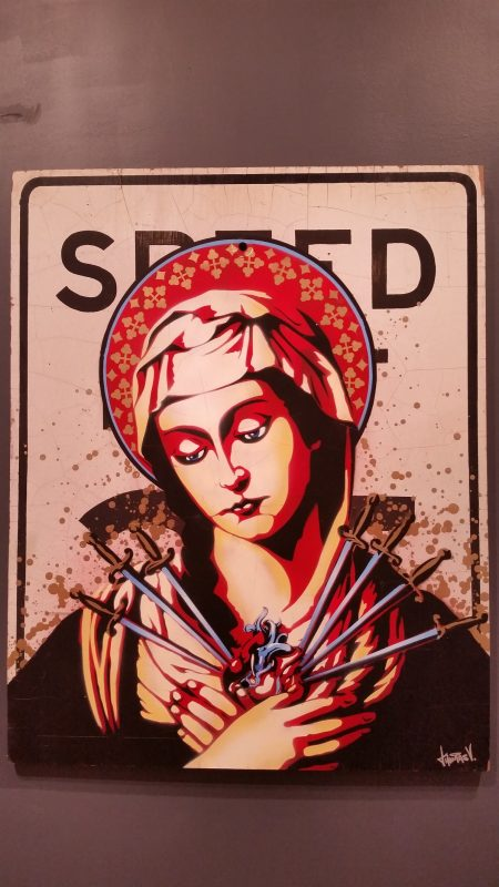 An old speed limit sign with a Virgin Mary image on it.