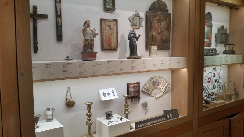 Antique religious art work in a glass display case at a museum in Santa Fe, New Mexico.