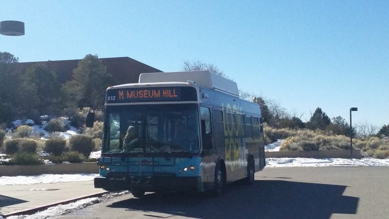 A city public transportation bus parked in front of Museum Hill in Santa Fe, New Mexico.
