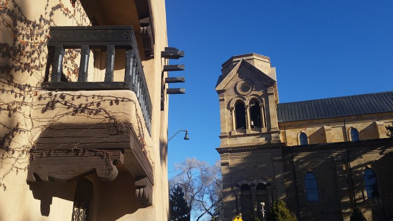 An adobe building and the bell tower of the Loretto Chapel in Santa Fe, New Mexico.