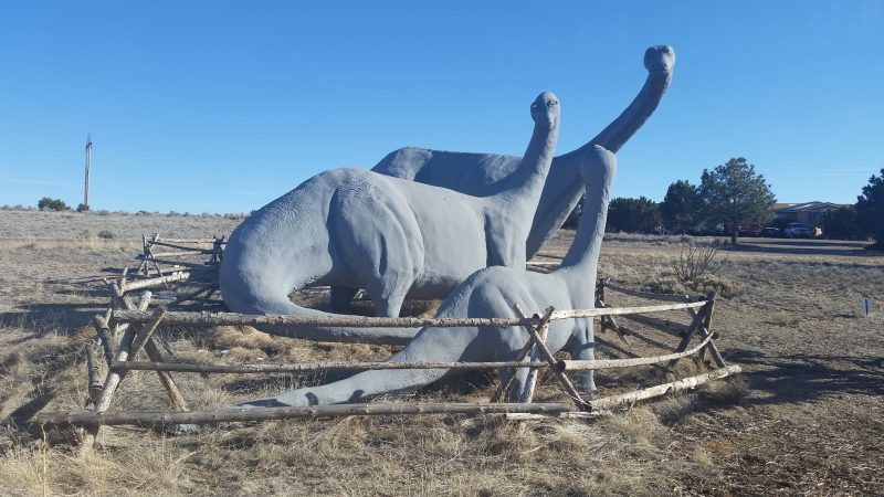 Three large grey Brontosaurus statue against a blue sky.