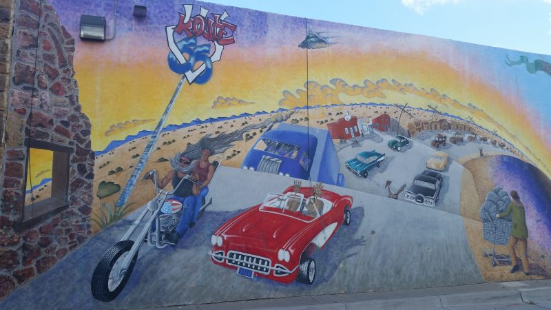 Painted wall mural of route 66 with red sports car and homeless person pushing a shopping trolley