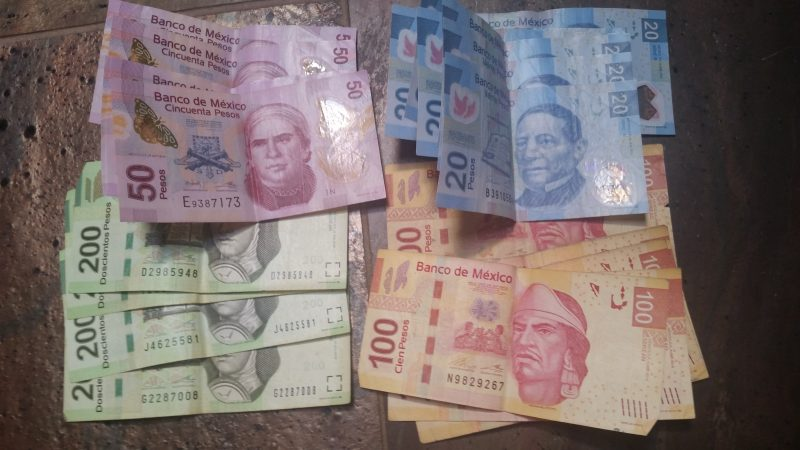 A pile of colorful Mexican peso notes on a tiled table top.
