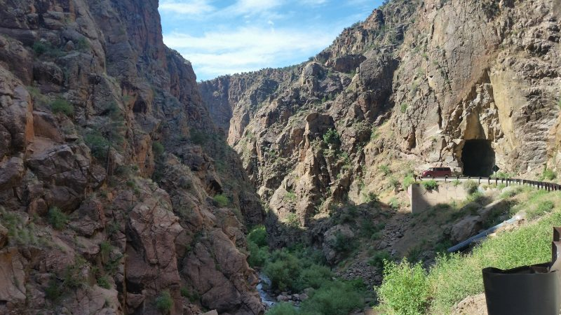 View of narrow Guadalupe Box Canyon with a burgundy van parked at the entrance of Gilman Tunnel north of Albuquerque.
