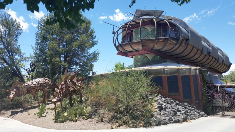 Spaceship like design house by Bart Prince with iron dinosaur sculptures in the front garden