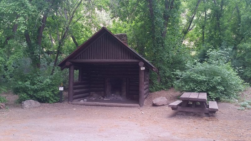 A three-sided shelter, picnic table and fire pit at Field Track Campground in Santa Fe National Forest, one of the more popular Pecos, NM camping spots in the area.