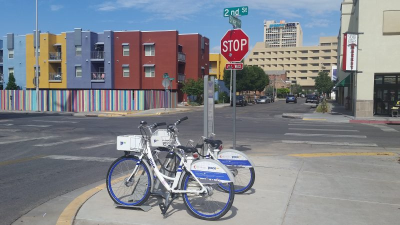 "Two blue and white ""pace"" bikes in Albuquerque parked in front of a stop sign with colourful buildings in the background."