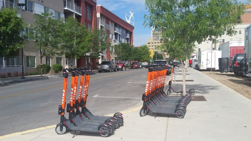 A row of orange Spin Scooters in Downtown Albuquerque with buildings in the background.