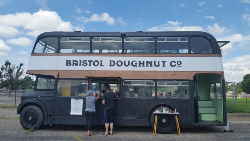 A unique black and white double decker bus in Albuquerque advertising Bristol Doughnut Co. with 2 people standing outside of bus.