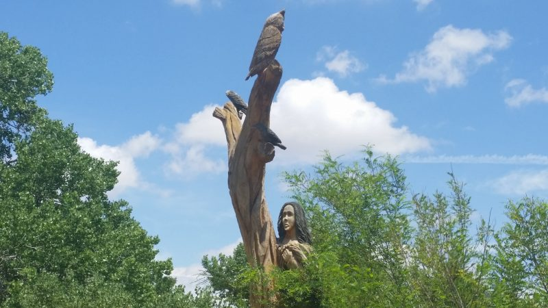 Tree stump carved with figure of an owl and a woman along the Rio Grande River in Albuquerque