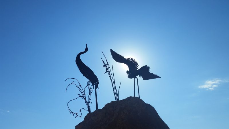 Silhouette of herons sculpture on a rock against a blue sky