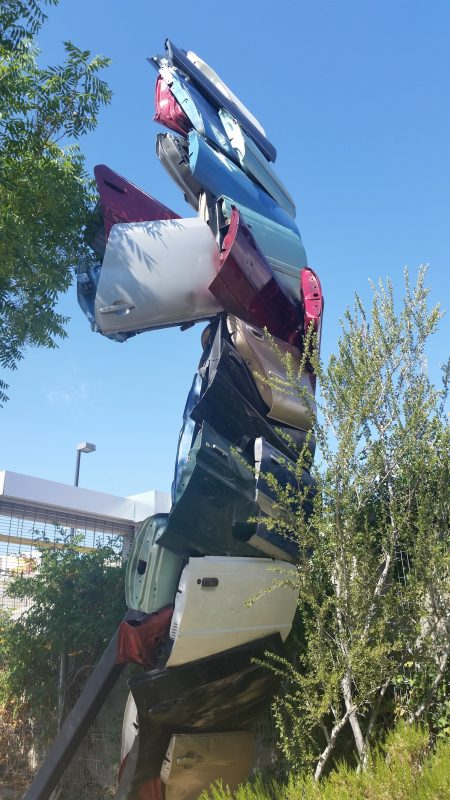 A unique tall totem pole-like sculpture made out of car doors in downtown Albuquerque.