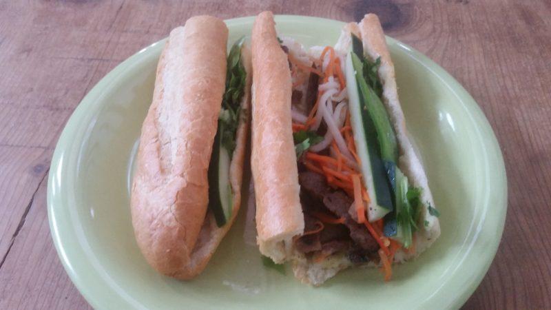 Baguette sandwich with vegetables and meat on a green plate from a Vietnamese restaurant in Albuquerque.