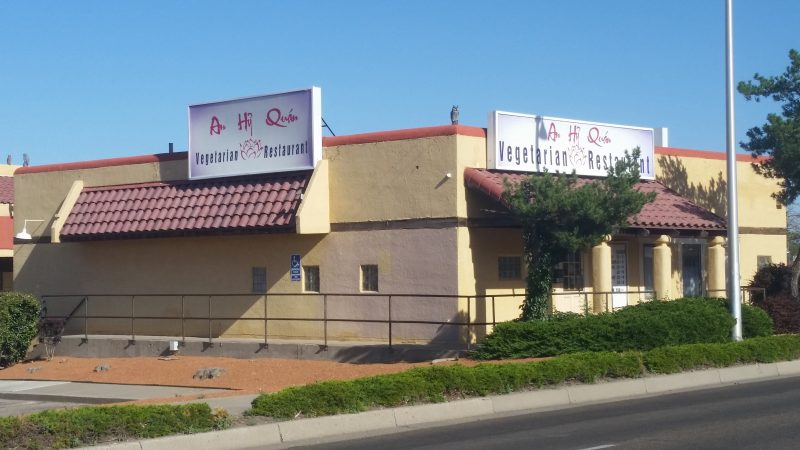 A beige building with a sign advertising itself as a vegetarian restaurant in Albuquerque, New Mexico.