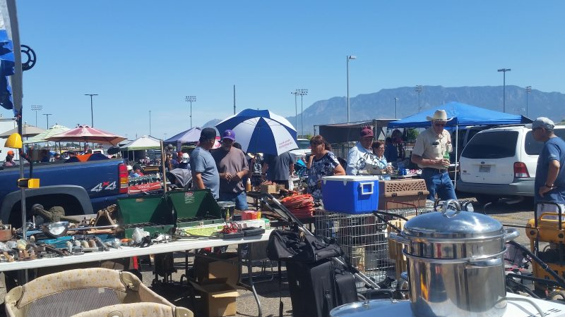 A jumble of items at a flea market in Albuquerque, including, a blue cooler, camping grills, a pet carrier and suitcases. Sandia mountains in the background.