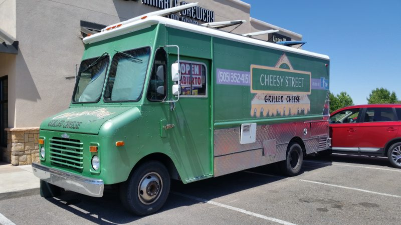 Green food truck with grilled cheese sandwich painted on the side.
