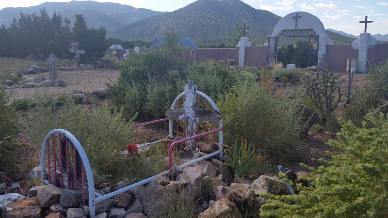 A graveyard in front of a church overgrown with weeds and cactus on the Turquoise Trail in New Mexico.