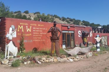 Assorted figures in front of a converted railroad car on the Turquoise Trail in New Mexico.