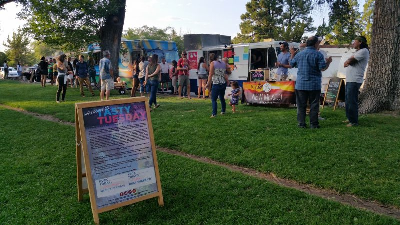 People lining up at food trucks for Tasty Tuesday at Hyder Park in Albuquerque, New Mexico.