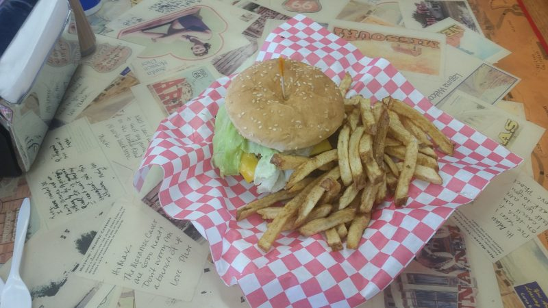 A green chile cheeseburger in a basket with french fries on the side, sitting on a table decorated with vintage postcards at Laguna Burger in Albuquerque.
