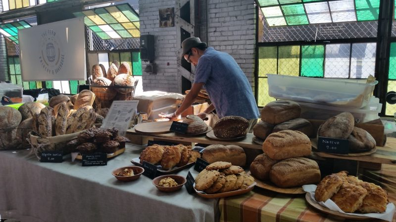 Man arranging baked breads at the Rail Yard Markets in Albuquerque with green and yellow stained glass windows behind him.