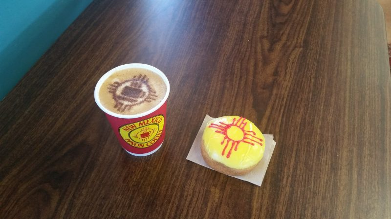 A cup of coffee with Zia symbol design in cinnamon in the froth, doughnut with yellow icing and red Zia symbol.