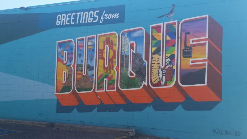 Blue wall painted with colourful mural saying Greetings from Burque.