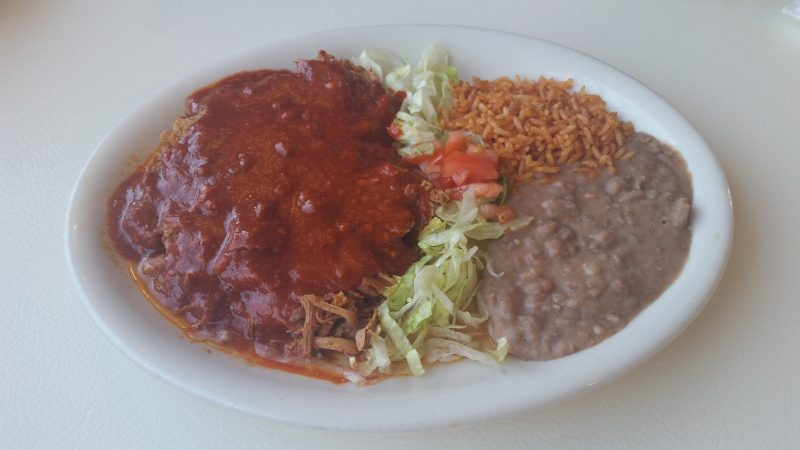 A plain white oval plate full of refried beans, rice, salad and shredded pork in a adovada red chile sauce from Mary and Tito's Cafe in Albuquerque.