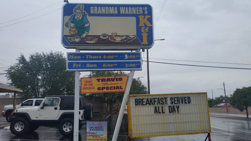 A sign for Grandma Warner's K & I Diner with two white vehicles behind it in Albuquerque, New Mexico.