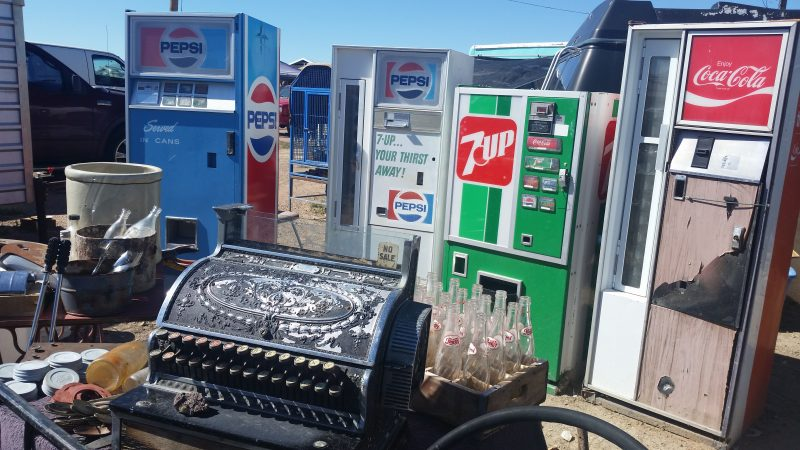 Vintage 7up and Pepsi vending machines and an old cash register at a flea market.