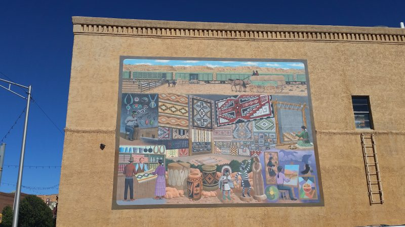 Colourful mural of Navajo traders and Navajo rugs on yellow brick building.
