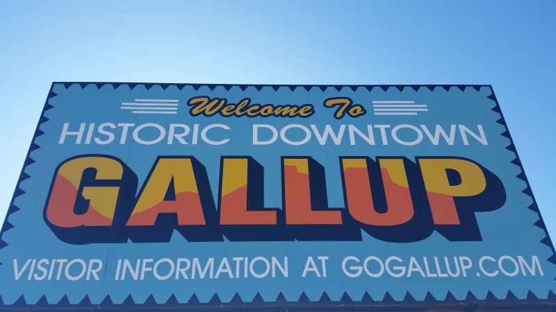 Blue billboard with orange and yellow writing saying welcome to historic downtown Gallup, New Mexico.