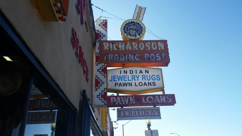 Neon sign for trading post in Gallup, New Mexico with Indian and a yellow arrow going through it.