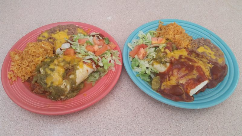 Two colorful plates of burritos with rice and beans on the side.