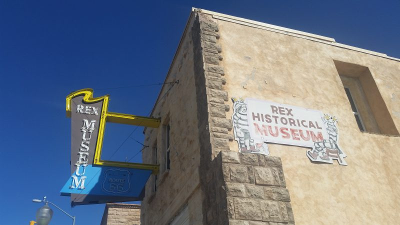 Yellow sandstone building with neon Rex Museum sign hanging outside a building in Gallup, New Mexico.