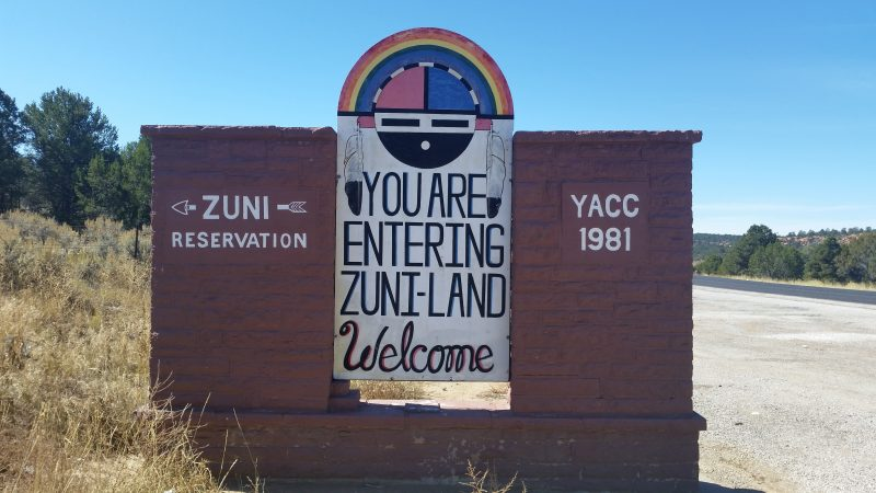 A sign with a traditional Zuni sunface symbol welcoming people to Zuni land, located on the Trail of The Ancients Scenic Byway in New Mexico.