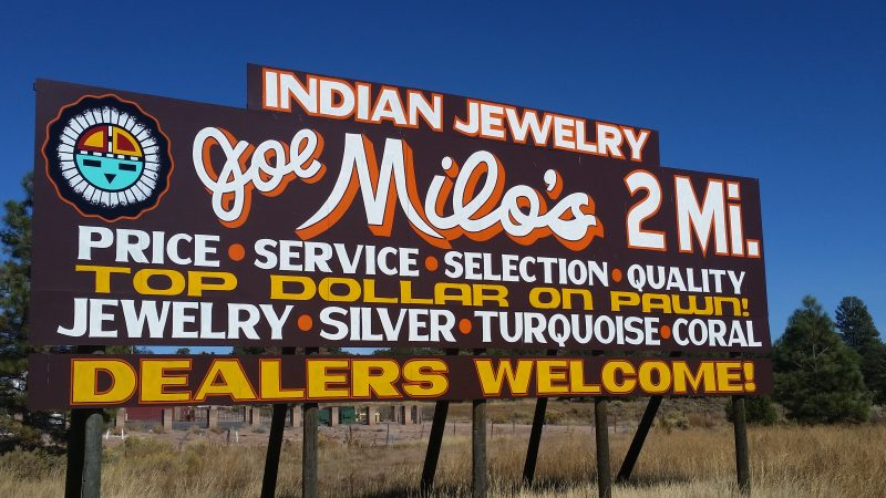 A brown sign with yellow and white lettering advertising Joe Milo's Trading Post, a popular weekend excursion in New Mexico for shoppers in search of native crafts.