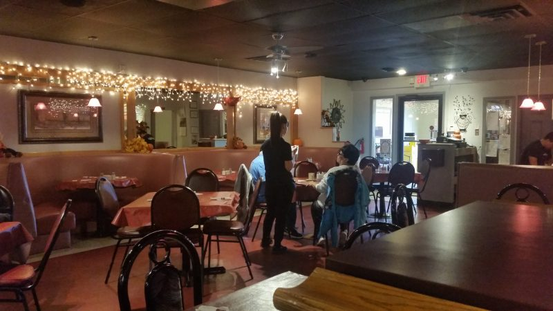 Interior of a restaurant in Gallup, NM with booths and a waitress serving customers at a table.
