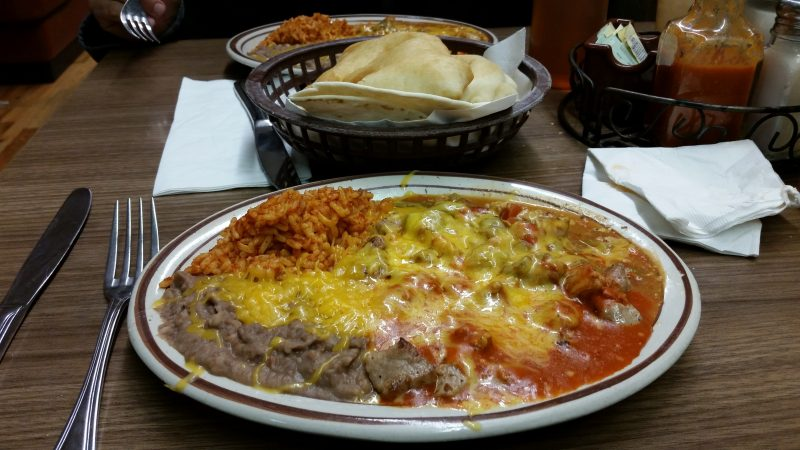 A plate of New Mexican food from a restaurant in Gallup, NM covered in red chile sauce and melted cheese.