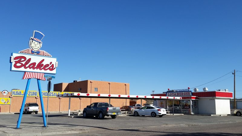 Tall sign of a man in a red and white striped jacket and blue top hat holding a sign advertising Blake's Lotaburger, one of the most recognized places to eat in Albuquerque.