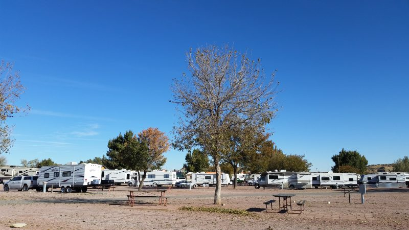 Caravans and RVs parked in an open lot with a couple of trees in Gallup, New Mexico.