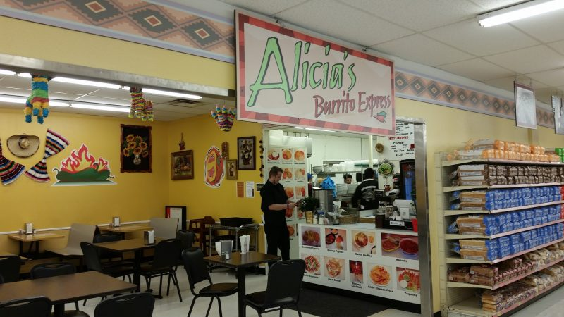 A burrito restaurant in Gallup, NM with a customer and employee at the counter.