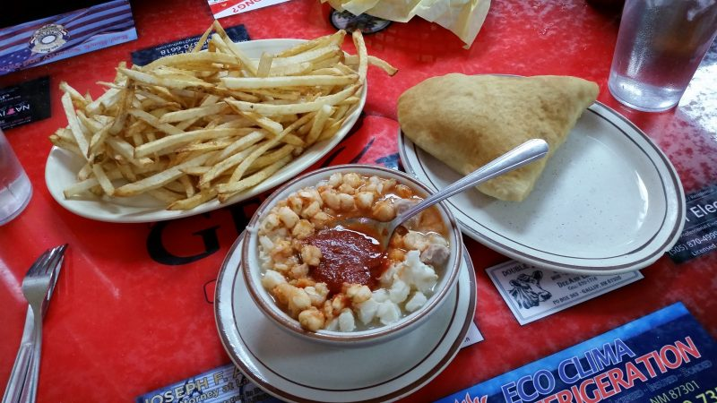 A bowl of red chile posole and a sopapilla next to a large plate of french fries from a restaurant in Gallup, NM.