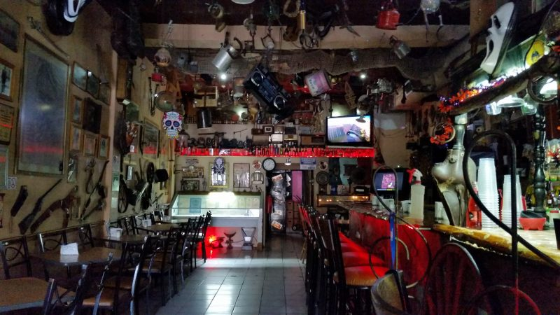 A bar in Chihuahua, Mexico with all sorts of random things hanging off the ceiling and walls.