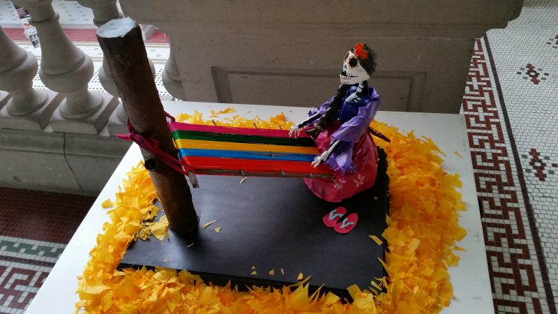 A papier mache figurine of a stylized skeleton weaving a brightly colored cloth.